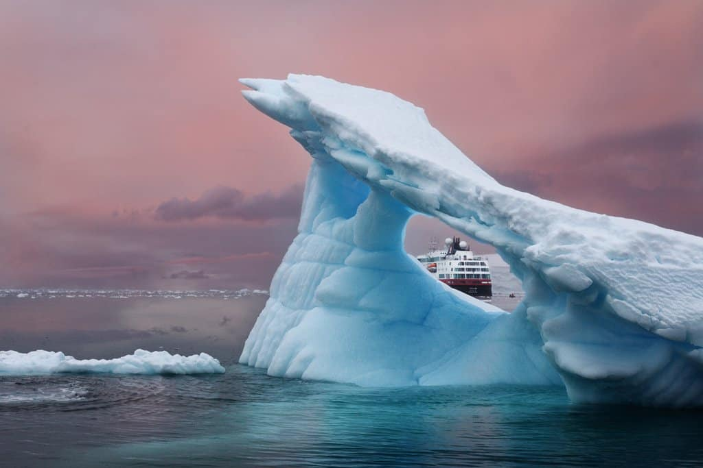 A beautiful scene of an iceberg and ship in Antartica