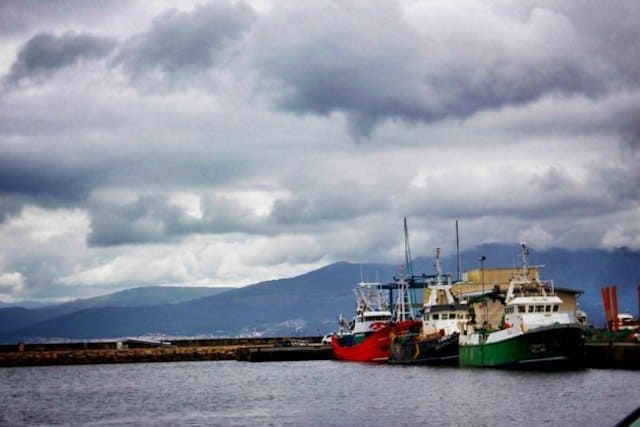 A row of colourful boats at Muros harbour