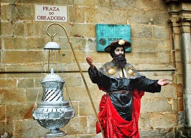A statue artist inspired by the ancient pilgrims uses a replica incense burner as a prop on the streets of Santiago de Compostela.